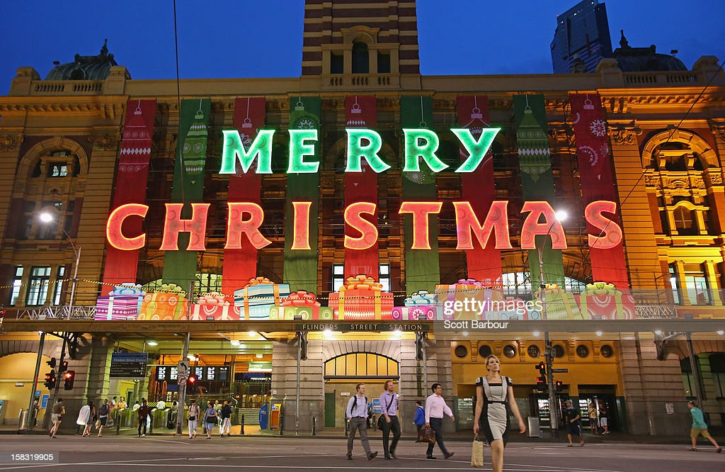 People walk past Flinders Street Station which displays a large 'Merry Christmas' sign as Melbourne lights up for Christmas on December 13, 2012 in Melbourne, Australia.