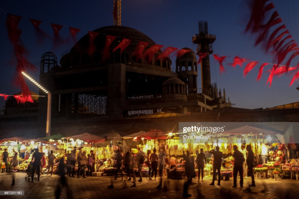 People walk past flower shops in front of the controversial Taksim Square Mosque on July 12, 2018 in Istanbul Turkey. Following Turkey's President Recep Tayyip Erdogan's re-election victory and the appointment of his son-in-law Berat Albayrak to lead the Treasury and Finance Ministry fears are growing that Turkey's economy is heading into crisis . The Turkish Lira, has plunged by approximately one-fifth this year raising prices for businesses and households.
