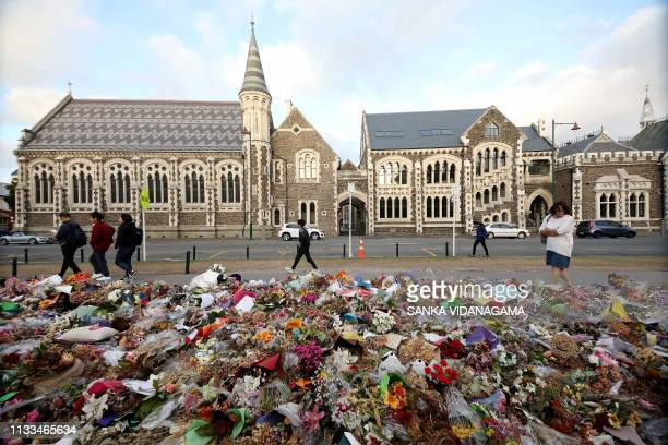 People walk past flowers and tributes displayed in memory of the twin mosque massacre victims outside the Botanical Gardens in Christchurch on March...