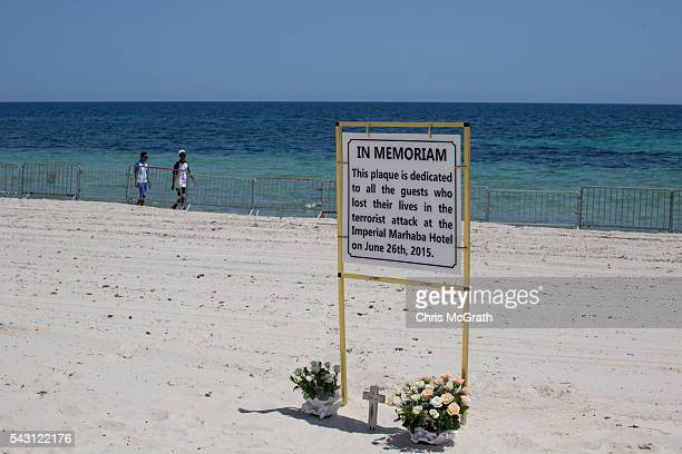 People walk past flowers placed by tourists underneath a memorial sign on the beach in front of the Imperial Marhaba hotel on June 26 2016 in Sousse...