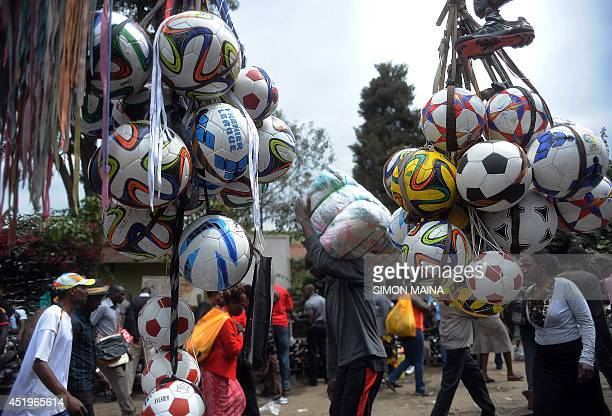 People walk past footballs displayed in Gikomba Market East Africa's biggest secondhand clothing market on July 10 2014 in Nairobi Locally known as...