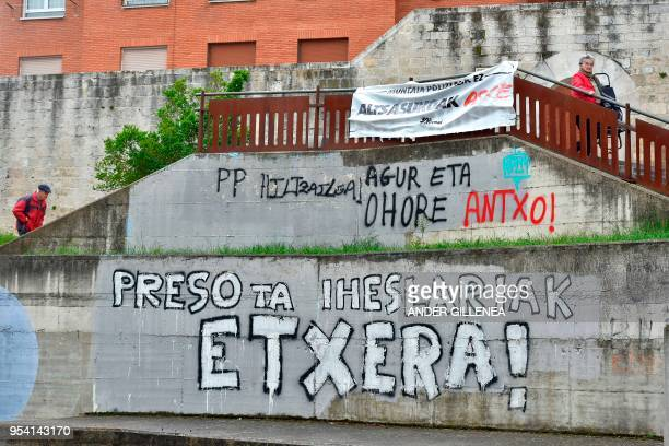 People walk past graffiti claiming ETA's prisoners back home in the Spanish Basque village of Agurain on May 3 2018 Spanish Prime Minister Mariano...