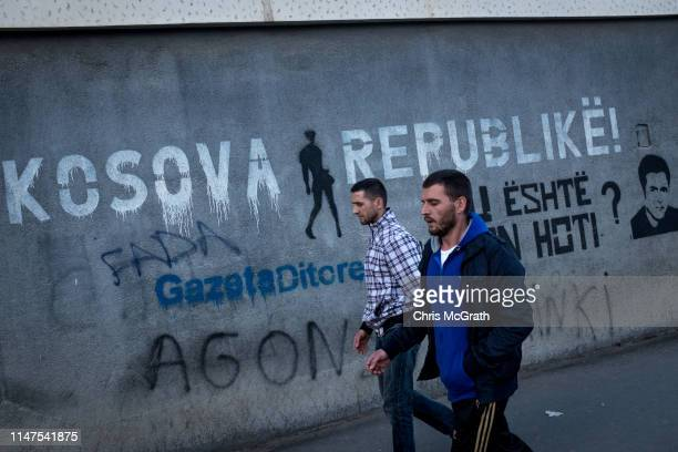 People walk past graffiti on May 3, 2019 in Pristina, Kosovo. A recent EU-backed summit failed to restart negotiations between leaders from Kosovo...