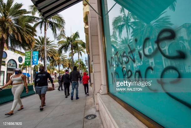 People walk past graffiti outside looted stores on the iconic Rodeo Drive after demonstrators protested the death of George Floyd in Beverly Hills...