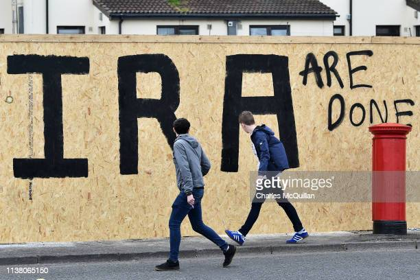 People walk past graffiti which says 'IRA are done' after journalist Lyra McKee was shot dead last night on Fanad Drive on April 19 2019 in...