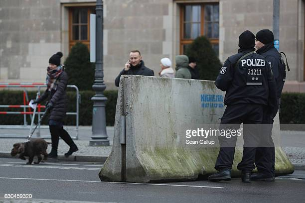 People walk past heavilyarmed police standing behind a concrete security barrier near the Brandenburg Gate prior to a concert there on December 23...