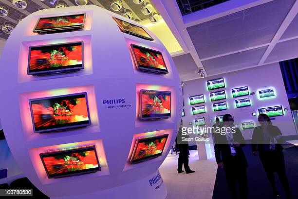 People walk past highdefinition 3D television screens at the 2010 IFA technology and consumer electronics trade fair at Messe Berlin on September 2...