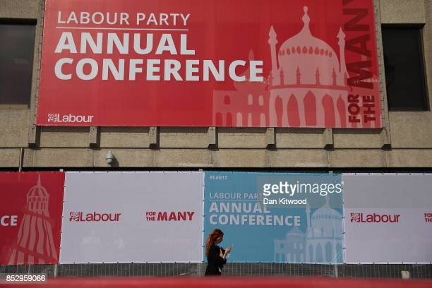 People walk past hoarding on the conference centre on Day One of the annual Labour Party Conference on September 24 2017 in Brighton England