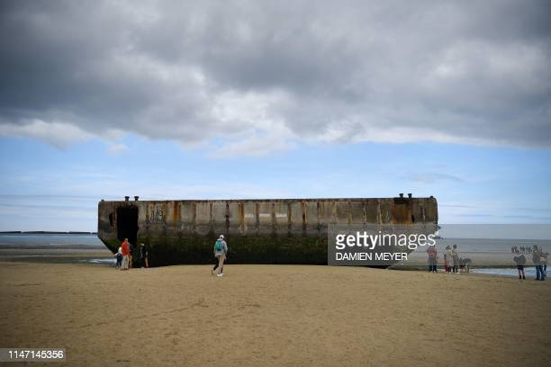 People walk past hollow concrete blocks at low tide as they visit the remains of Mulberry harbour which comprised of floating roadways and pier heads...