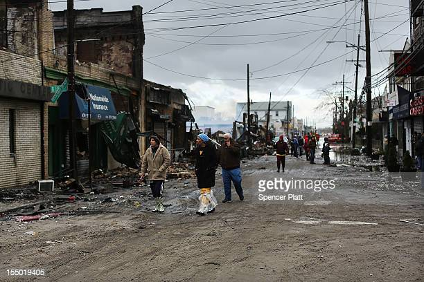 People walk past homes and businesses destroyed during Hurricane Sandy on October 30, 2012 in the Rockaway section of the Queens borough of New York...