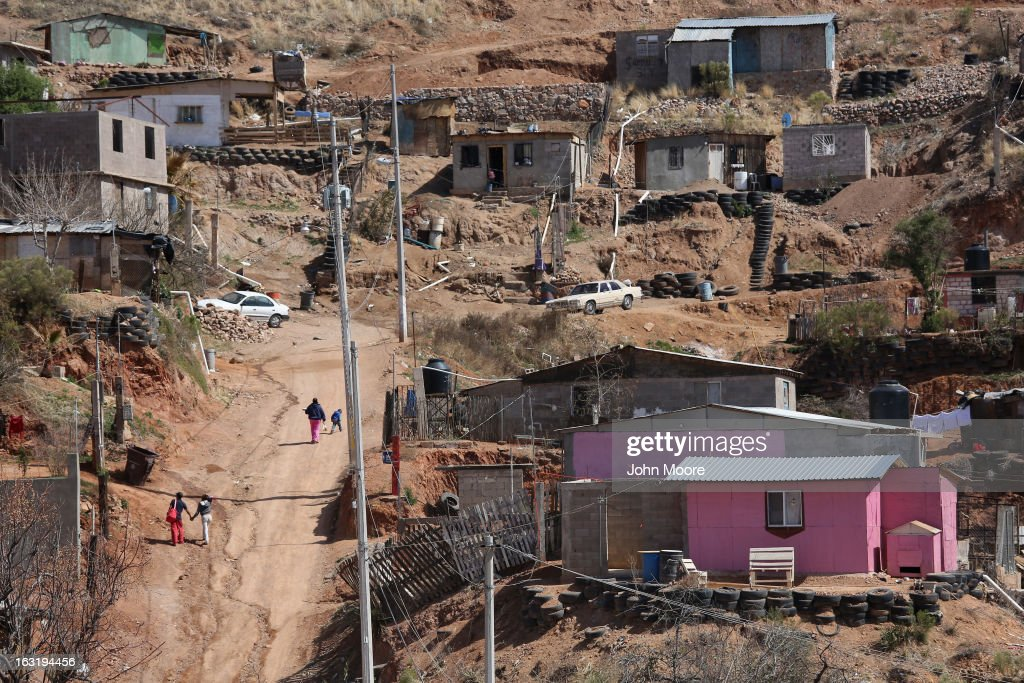 People walk past homes near the Tirabichi garbage dump on March 5, 2013 in Nogales, Mexico. About 30 families live inside the Tirabichi garbage dump, searching for recyclables to sell for a living.