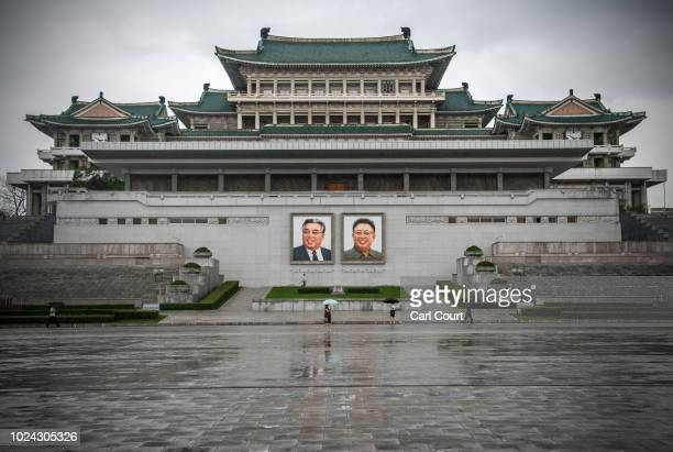 People walk past huge pictures of Kim Il-sung and Kim Jong-il displayed from the Parade Reviewing Stand, in front of the Grand People's Study House,...