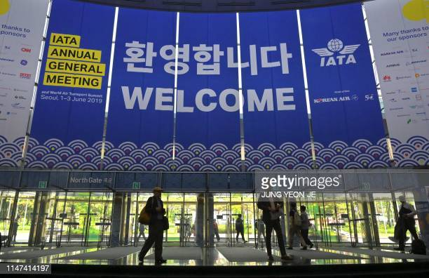 People walk past IATA banners during the annual general meeting of International Air Transport Association at COEX convention and exhibition centre...