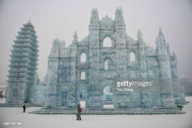 People walk past ice sculpture amid heavy air pollution on January 13 2019 in Harbin China Meteorological authorities have issued an orange alert for...