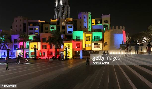 People walk past illuminated buildings on Burj Plaza in downtown Dubai with in the background the Address Downtown Dubai tower early on March 24 2014...