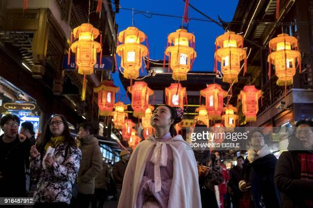 People walk past lantern decorations in Yu Yuan Garden in Shanghai on February 10 ahead of the coming Lunar New year marking the Year of the Dog The...