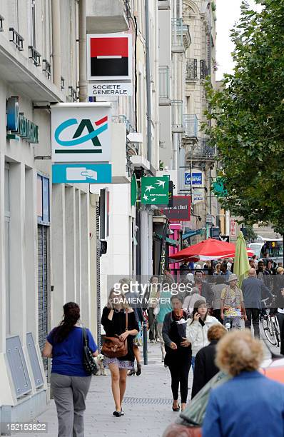 People walk past logos of French banks Societe Generale Credit Agricole and BNP Paribas on agencies' frontdoors on September 12 2011 in Rennes...