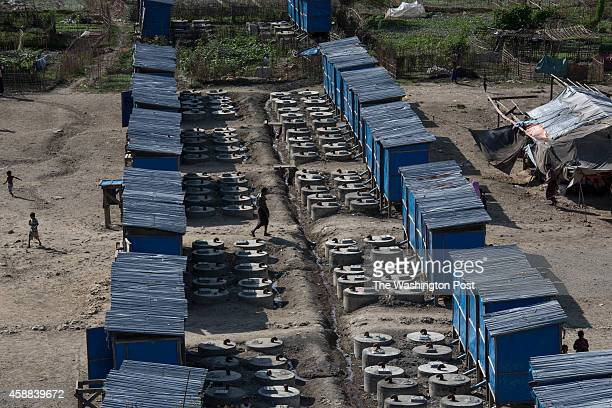 People walk past makeshift latrines at the Mayebon IDP camp where registration has taken place forcing the residents of the camp to list themselves...