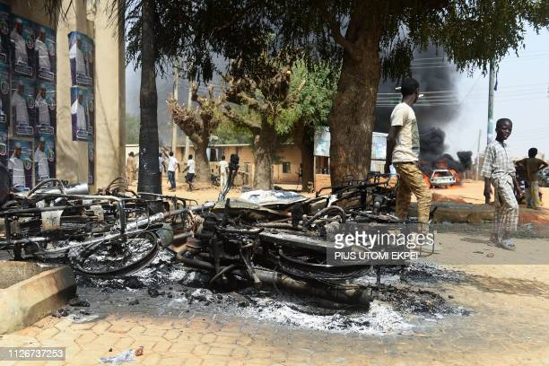 People walk past motorcycles burnt following deadly clashes between supporters of the ruling All Progressives Congress and the opposition Peoples...