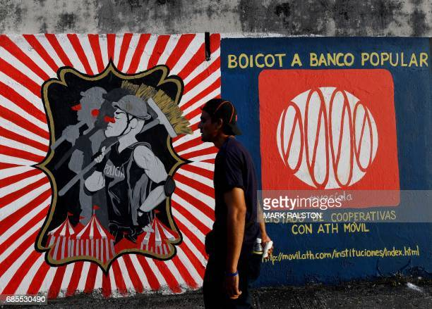 People walk past murals protesting the state of economy on May 15 2017 in San Juan Puerto Rico as the former Spanish colony of 35 million now a US...