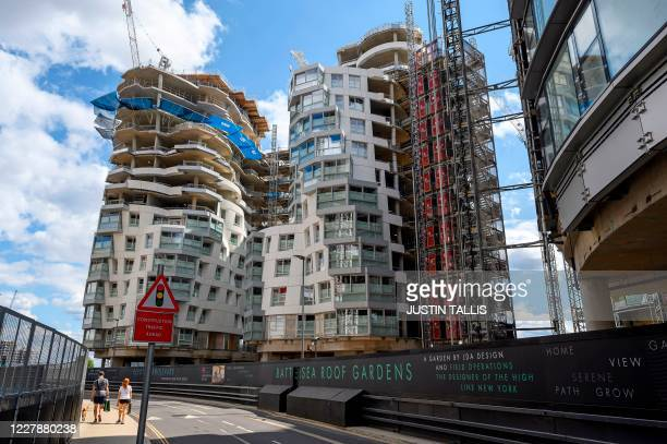People walk past new apartments and a retail complex under constuction at the Battersea Power Station redevelopment site in south London on August 2...