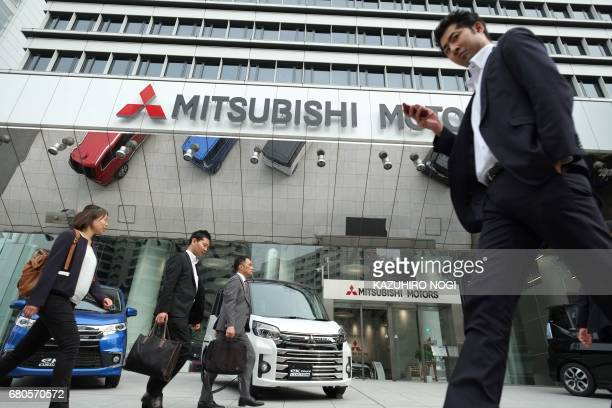People walk past new cars of Japan's Mitsubishi Motors Corporation on display at the company's head office in Tokyo on May 9 2017 Mitsubishi Motors...