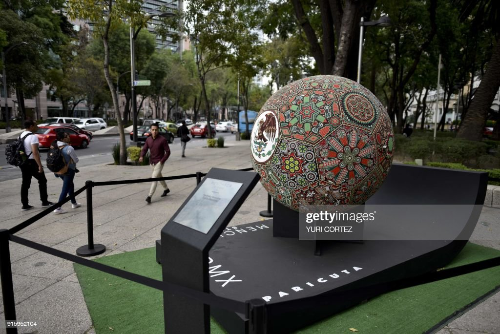 People walk past next to a football ball sculpture made of fiberglass and worked in Huichol art and called 'Henttsika Mexicano' (Sueno Mexicano in Spanish) and placed along Reforma avenue as part of an exposition called 'Exposicion Huichol Mas Grande del Mundo' in Mexico City , on February 8, 2018. One hundred Wixarikas artists from the social and cultural company Paricuta made 10 monumental works of art inspired by sports and nature and are exposed to the public at the street. /