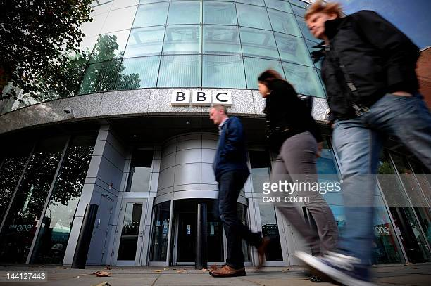 People walk past one of the entrances to the BBC Television offices in west London on October 6 2011 The British Broadcasting Corporation said on...