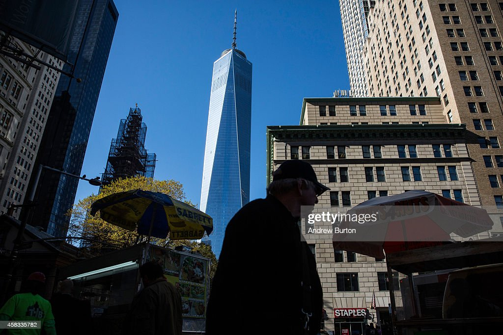 People walk past One World Trade Center, which opens today, on November 3, 2014 in New York City. The skyscraper is 104 stories tall and cost $3.9 billion; it opens more than 13 years after the terrorist attacks of September 11, 2001, destroyed the original World Trade Center buildings. Officials say the building is currently at 60% occupancy, with Conde Nast as one of the first major tenants to move in.