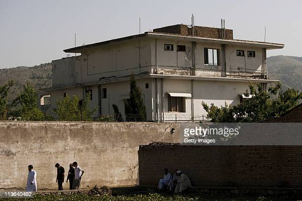 People walk past Osama Bin Laden's compound, where he was killed during a raid by U.S. Special forces, May 3, 2011 in Abottabad, Pakistan. Bin Laden...