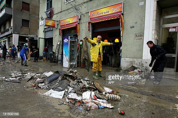 People walk past part of cars and debris in a street of Genoa after heavy rainfall on November 5 2011 Six people were killed the day before when the...