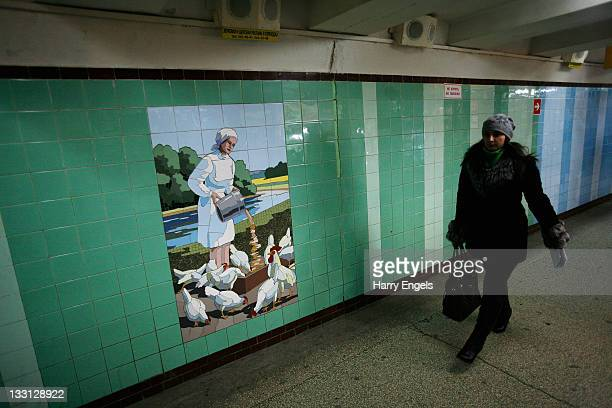 People walk past pieces of Socialist Realist art painted on the walls of an underpass on November 17 2011 in RostovnaDonu Russia RostovnaDonu is one...
