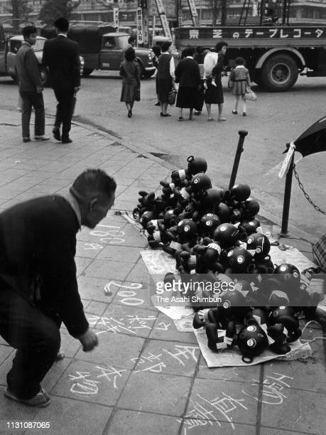 People walk past piles of Dakkochan dolls on the street as the boom has been gone past on October 15 1960 in Tokyo Japan