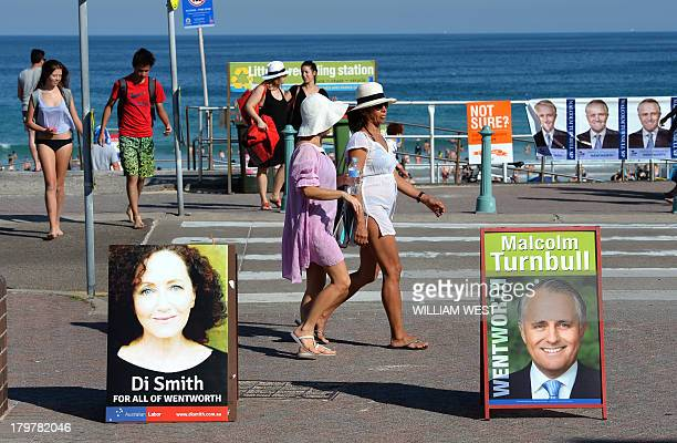 People walk past political posters outside a polling booth at Sydney's Bondi Beach on September 7 2013 Australians are voting in their general...