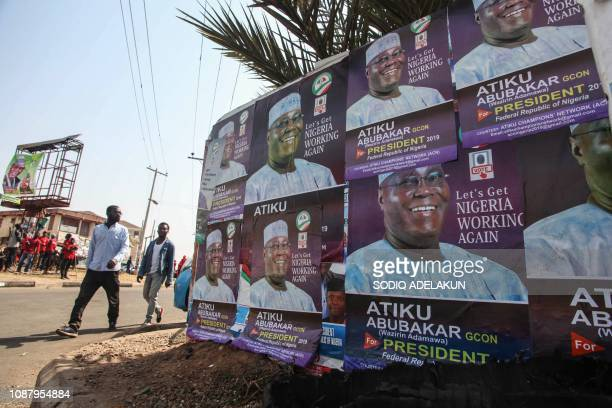 People walk past posterd of Nigerian opposition presidential candidate of the People's Democratic Party Atiku Abubakar hold his portrait during a...