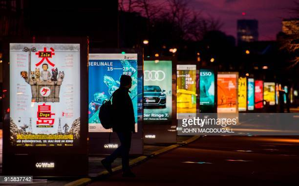 People walk past posters advertising the upcoming Berlinale film festival including the festival's opening film Isle of Dogs by Wes Anderson at...