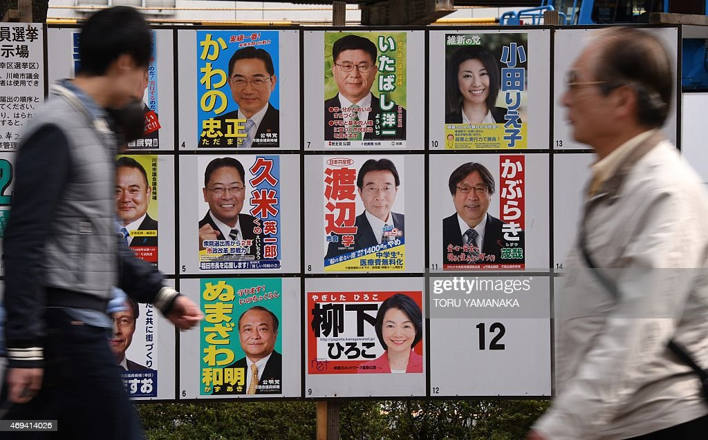 People walk past posters of candidates for the Kawasaki City Assembly in Kawasaki, suburbun Tokyo, on April 12, 2015. Japan on April 12 held nationwide local elections, partially seen as a referendum on Prime Minister Shinzo Abe's efforts to boost the country's economy with upper house elections due next year. AFP PHOTO / Toru YAMANAKA