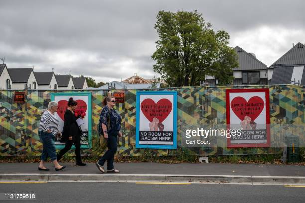 People walk past posters put up in the aftermath of the attack, on March 21, 2019 in Christchurch, New Zealand. 50 people were killed, and dozens are...