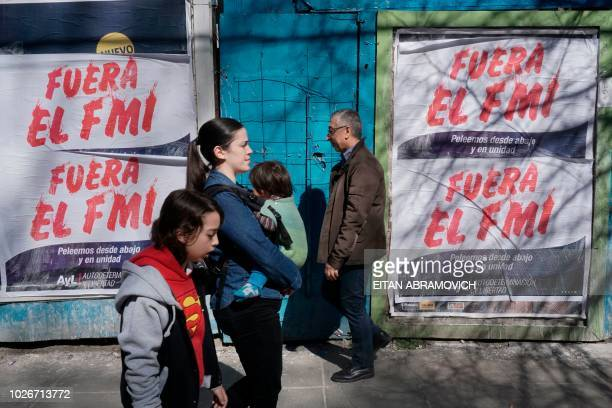 People walk past posters rejecting the government's negotiations with the International Monetary Fund in Buenos Aires on September 4 2018 Argentina's...
