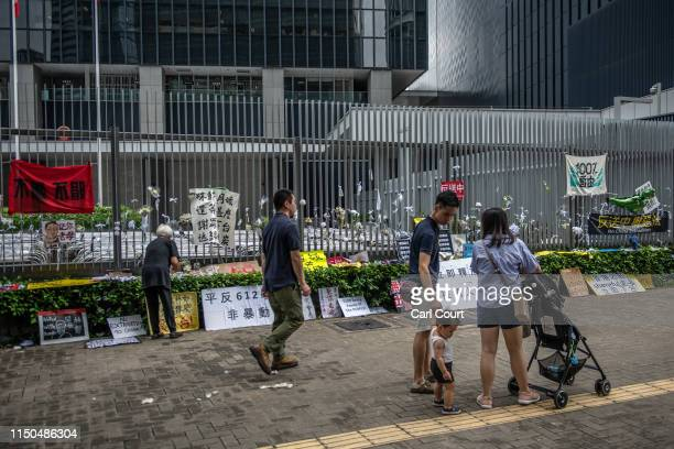 People walk past protest banners hung on the fence of the Legislative Council building on June 18 2019 in Hong Kong Hong Kongs Chief Executive Carrie...