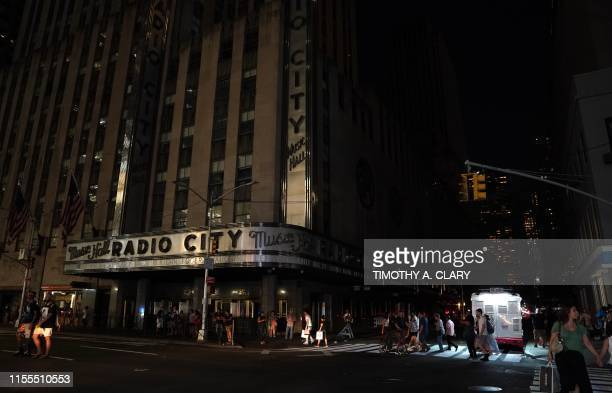 TOPSHOT People walk past Radio City Music Hall in the dark during a major power outage affecting parts of New York City on July 13 2019 Subway...