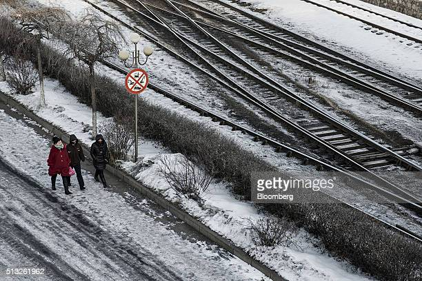 People walk past rail tracks in the Erdaojiang district in Tonghua Jilin province China on Wednesday Jan 6 2016 The city's oncevaunted staterun steel...