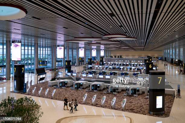 People walk past rows of self check-in counters at the departure hall of Changi Airport on March 23, 2020 in Singapore. Singapore is imposing a ban...