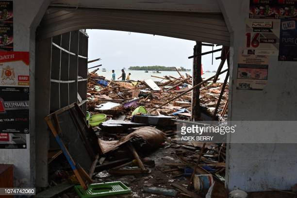 People walk past rubble in the Sumber Jaya village in Sumur, Pandeglang, Banten province on December 25 three days after a tsunami - caused by...
