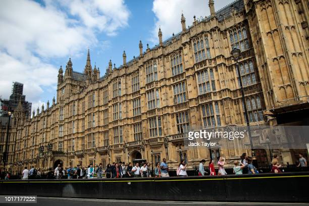 People walk past security barriers outside the Houses of Parliament following yesterday morning's incident which is being investigated by terror...