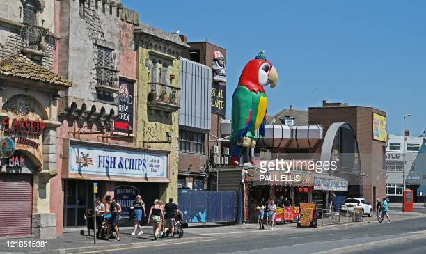 People walk past shops in the warm sunshine in Blackpool on the north-west coast of England on May 31, 2020 on the eve of a further relaxation of the...