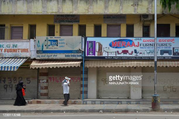 People walk past shops with closed shutters along a road as a lockdown is in effect to curb the spread of Covid-19 coronavirus in Bangalore on May...