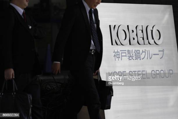 People walk past signage for Kobe Steel Ltd displayed outside the company's offices in Tokyo Japan on Friday Oct 27 2017 Kobe Steel said yesterday it...