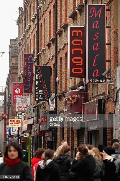 People walk past signs for businesses on Brick Lane which is synonymous with curry restaurants March 16 2011 in London England From April 2011 the...