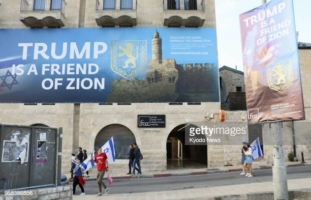 People walk past signs in Jerusalem on May 13 that show support for US President Donald Trump's decision to move the country's Embassy to the city...